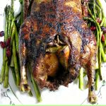 Overhead photo of a whole Crispy Roast Duck on a white platter with asparagus and cranberries