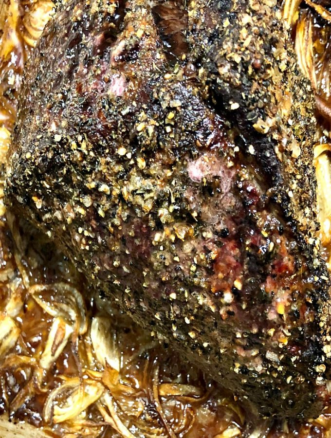 close up photo of roast beef in a baking pan with roasted onions