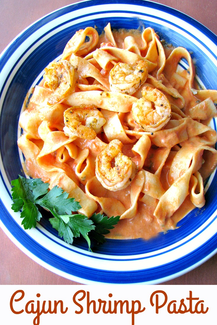 photo of a blue rimmed plate of Cajun Shrimp Pasta with pappardelle pasta and creamy tomato sauce