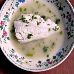 photo of a flower trimmed bowl with a piece of Poached Haddock in Herbed Broth