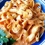Close up photo of plated Cajun Shrimp Pasta on a blue rimmed plate