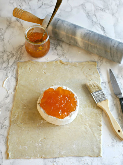 photo of cheese topped with apricot preserves on topped of puff pastry dough