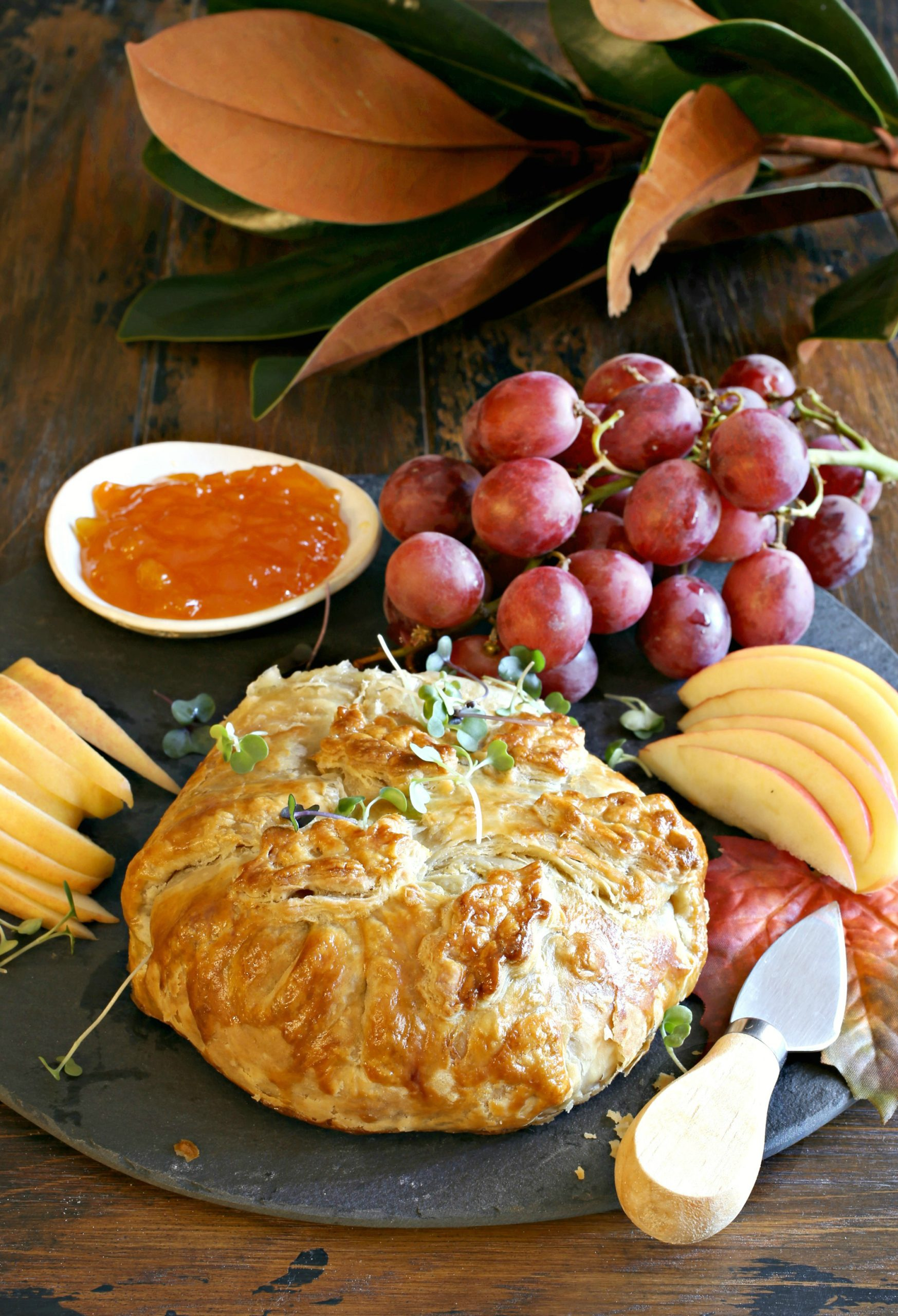 photo of baked brie on a board with fresh grapes apricot preserves and sliced apples on the side