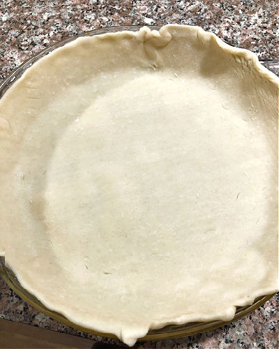 photo of an unbaked pie crust in a pan