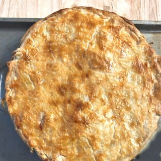 photo of a whole pot pie on a baking sheet on top of a wood table