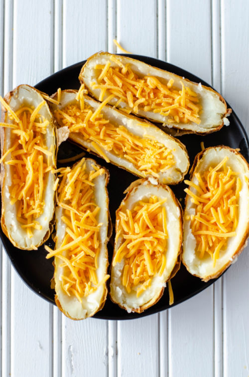 cheese topped potato skins on a black plate