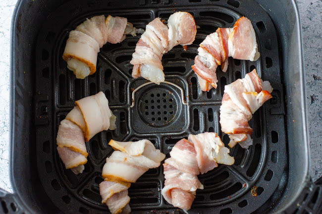 bacon wrapped raw shrimp in the base of an air fryer
