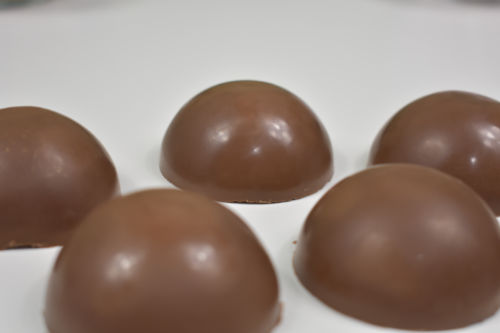 hardened chocolate bomb halves on a white plate