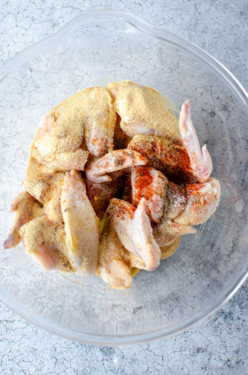 photo of seasoning on chicken wings in a glass bowl