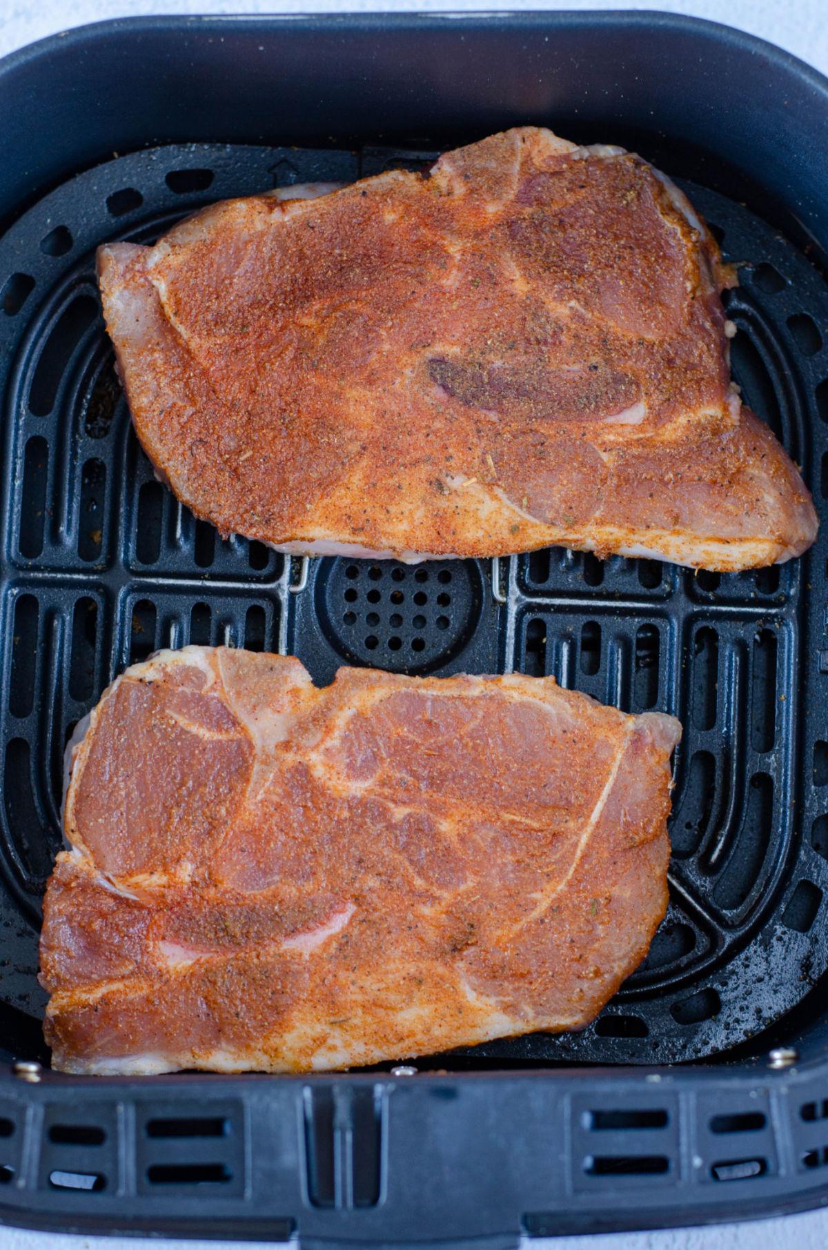 seasoned uncooked pork chops in an air fryer